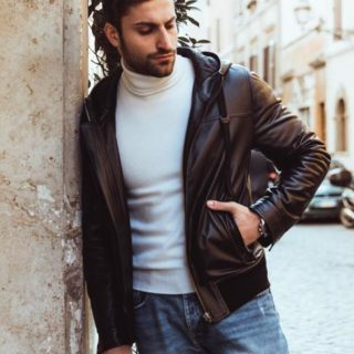 Dolce is sportive black man lambskin jacket with hood an quilted lining. It is tailored and very fitted with an elastic at the bottom.